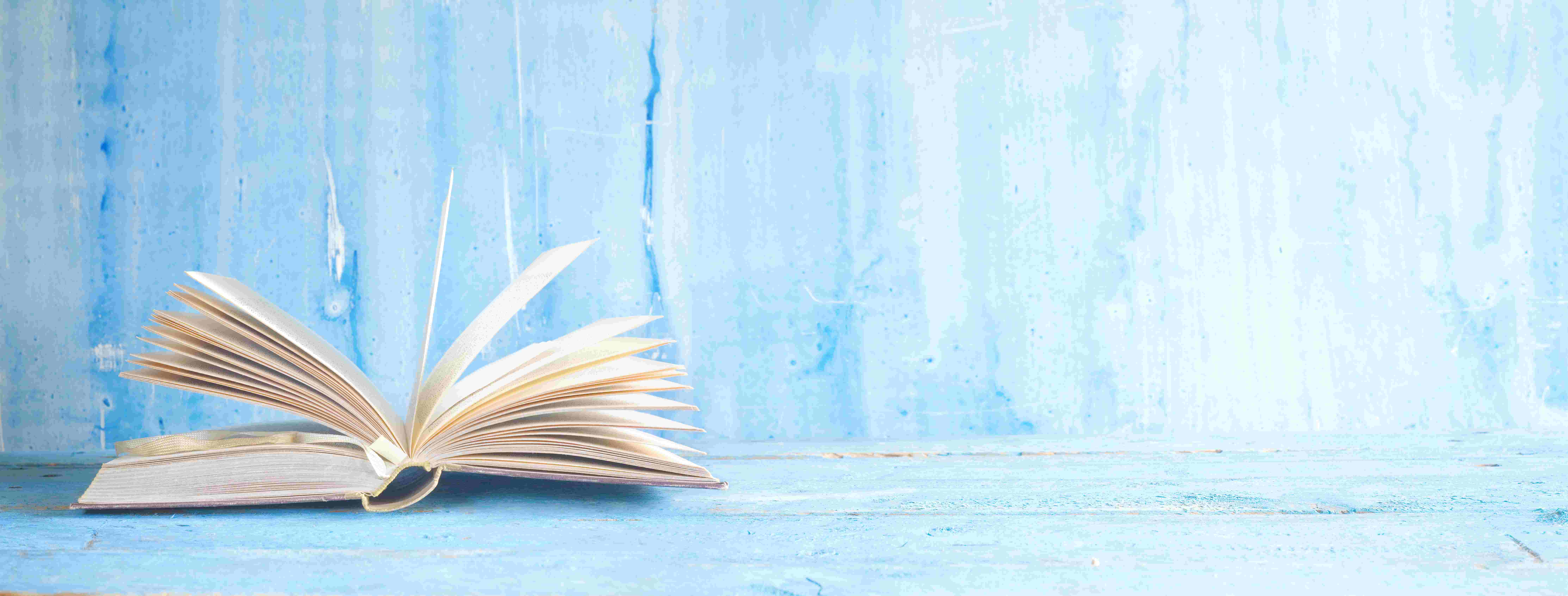 opened-book-on-blue-grungy-background-panoramic-good-copy-space
